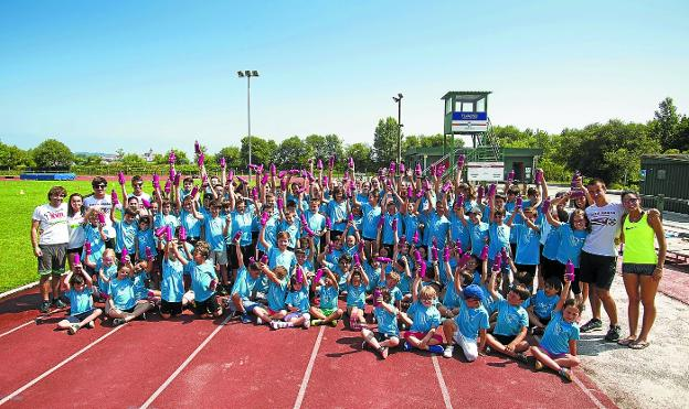 Los niños y jóvenes de los cursillos de atletismo, junto a monitores de Bidasoa Atletiko Taldea, durante uno de los descansos. /F. DE LA HERA