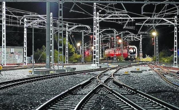 Vegetación, vías, torretas, catenarias, oscuridad iluminada; el último tren de la noche entra en los depósitos de Euskotren en Araso./ Lobo Altuna
