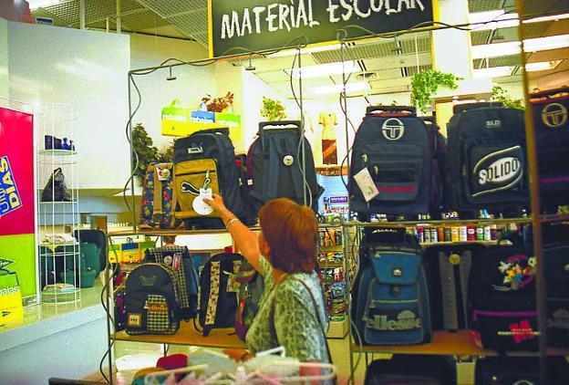 Una mujer observa el precio de una mochila en un establecimiento de material escolar. /  MORQUECHO