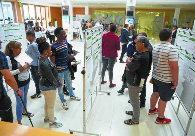 Asistentes a la Semana del Empleo observan las ofertas de trabajo expuestas en Ficoba. / F. DE LA HERA