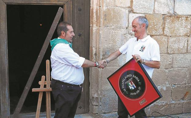 Rafa González Merino recibe la felicitación del presidente de Alde Zaharra-San Juan Auzo Elkartea, Koldo Susperregi./