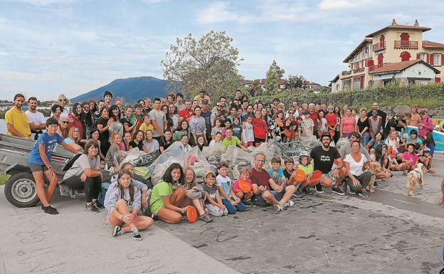 Voluntarios. Los participantes en la quedada convocada por @recicla_birziklatu posan tras realizar la limpieza del río Bidasoa. /