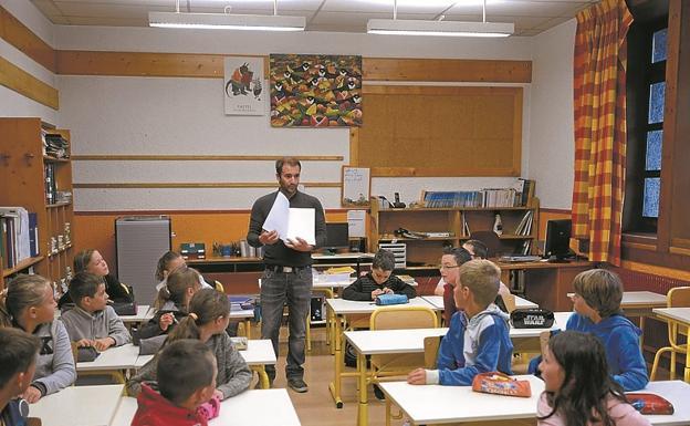 Alumnos atienden a su profesor en una clase./