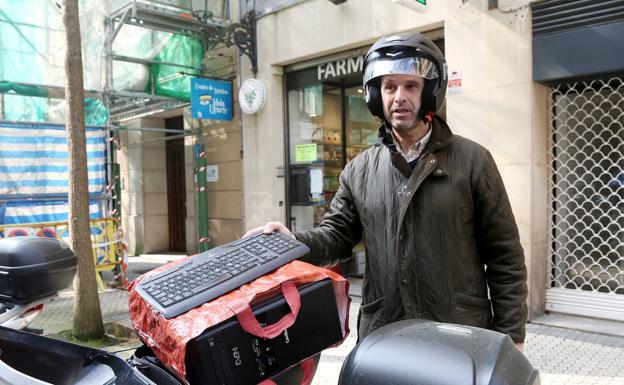 Alvaro, en la calle Garibay, mete el ordenador en la moto para teletrabajar en casa los próximos días.
