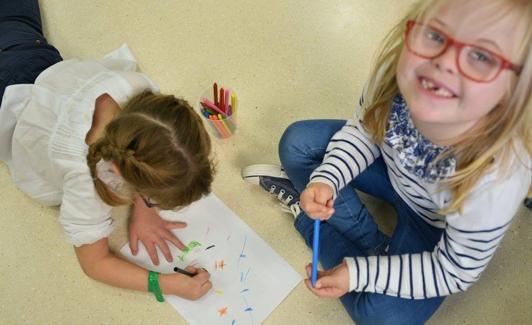 Una niña con trisomía 21 dibuja junto a una compañera sin discapacidad.
