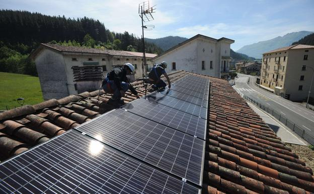 Two workers install solar panels on the roof of a building in Oñati.